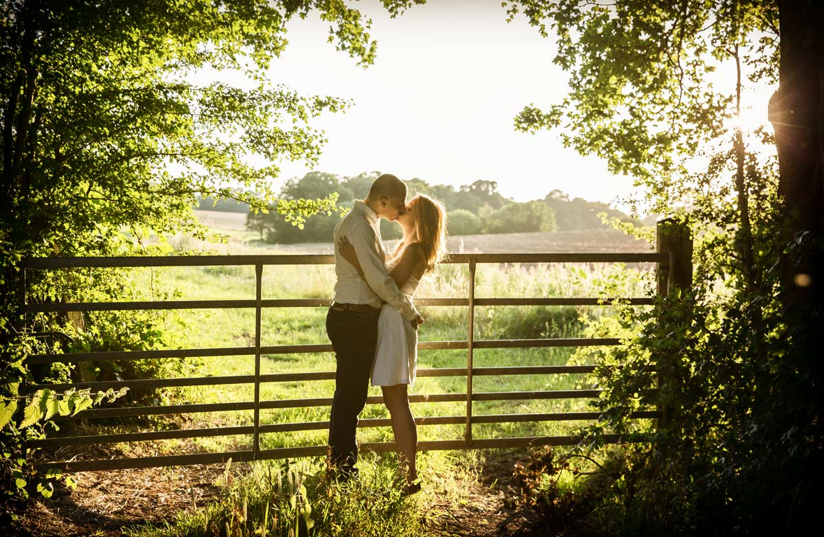 couple kissing by field gate