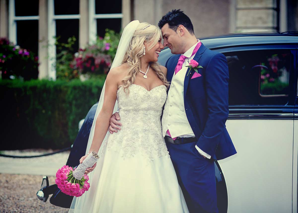 head to head in front of wedding car image