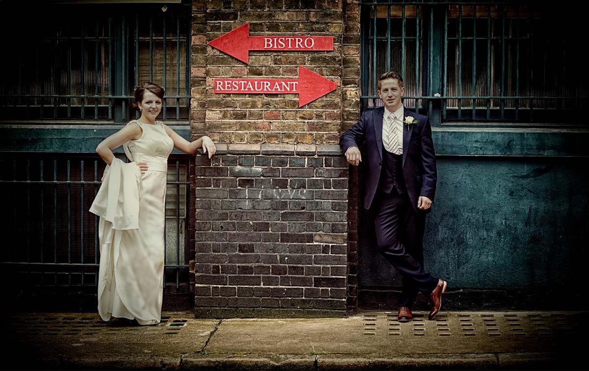 posing against wall on London wedding day