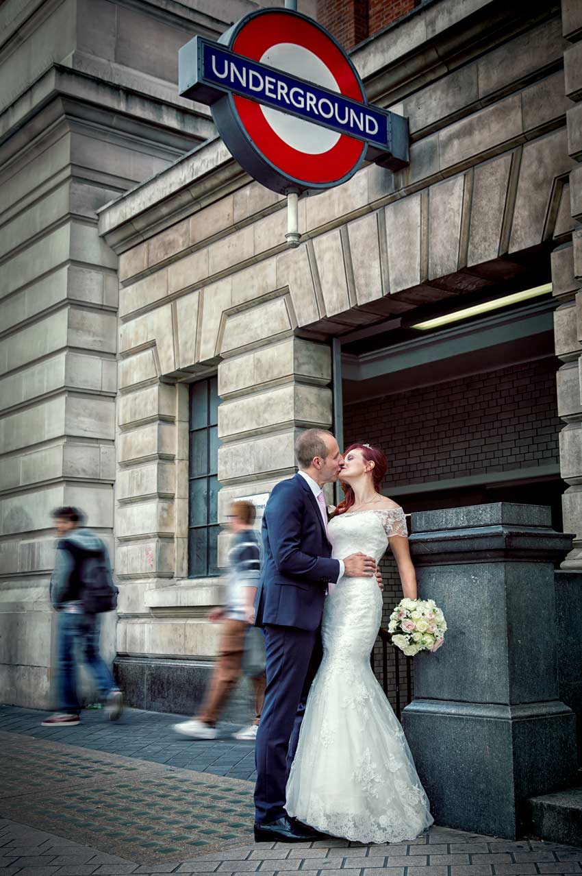 Kissing after wedding outside Kensington tube station