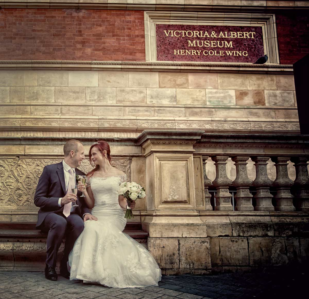 Wedding couple toast on bench outside Victoria and Albert Museum
