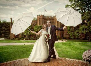 wedding couple celebrate in rain Leez Priory