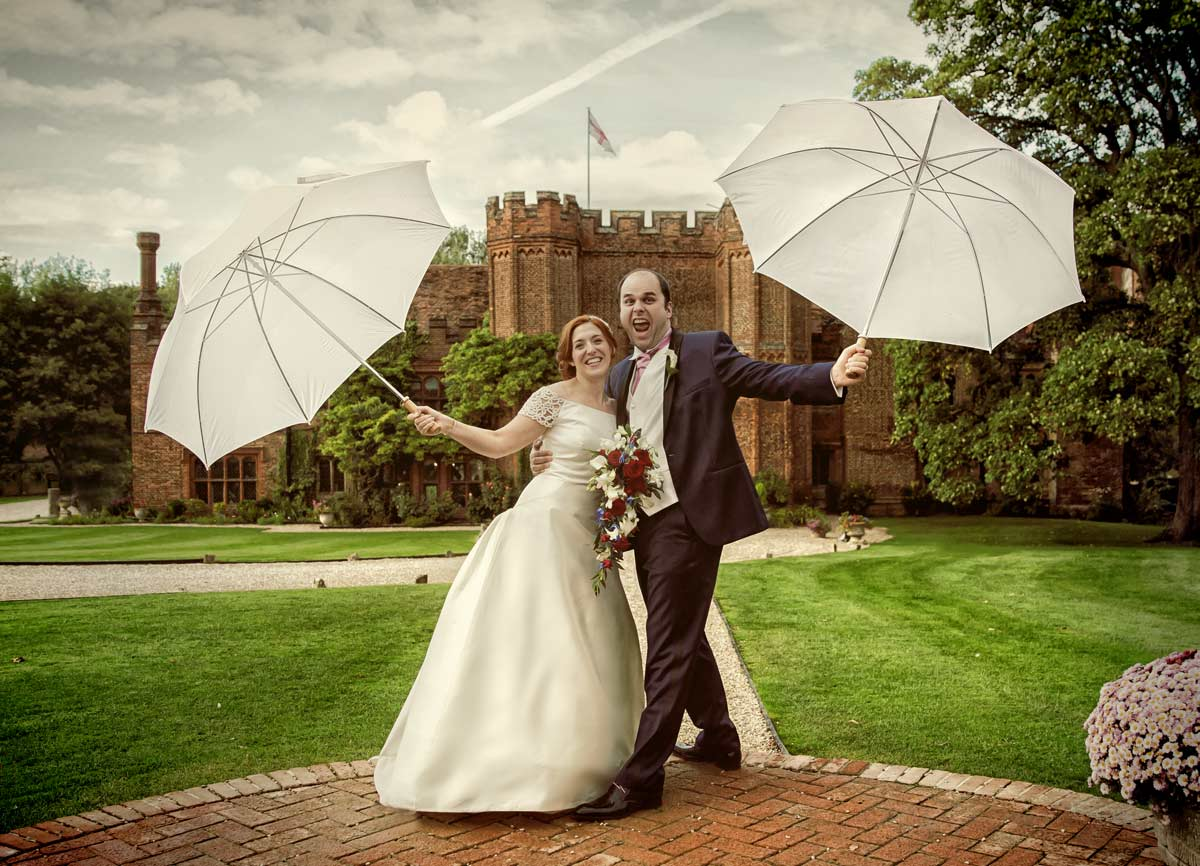 wedding couple celebrate in rain Leez Priory