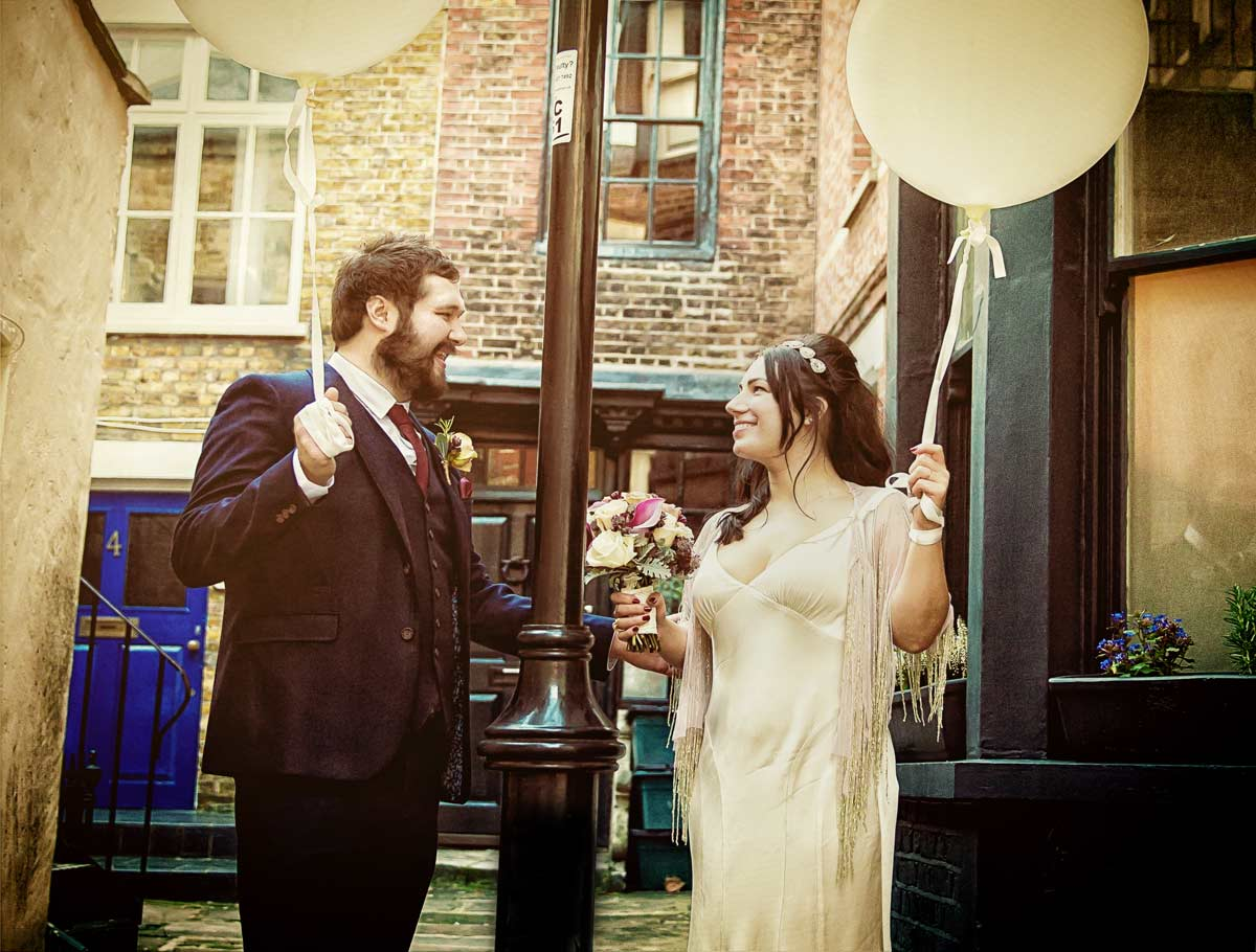 Bride and groom hold wedding balloons Londons Islington borough
