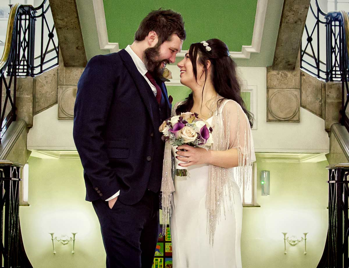 Couple smile on stairs inside for Islington Town Hall wedding photographer