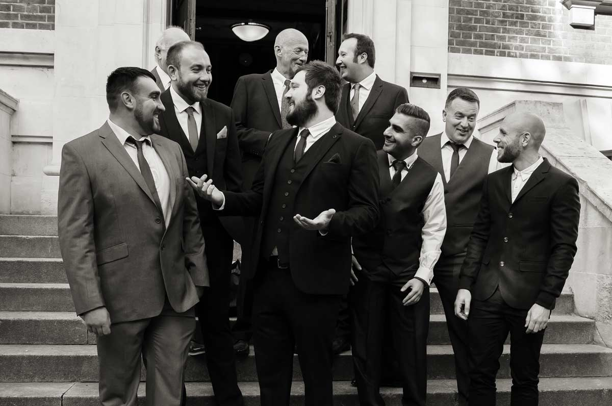 Groomsmen chat on the steps of Islington town hall