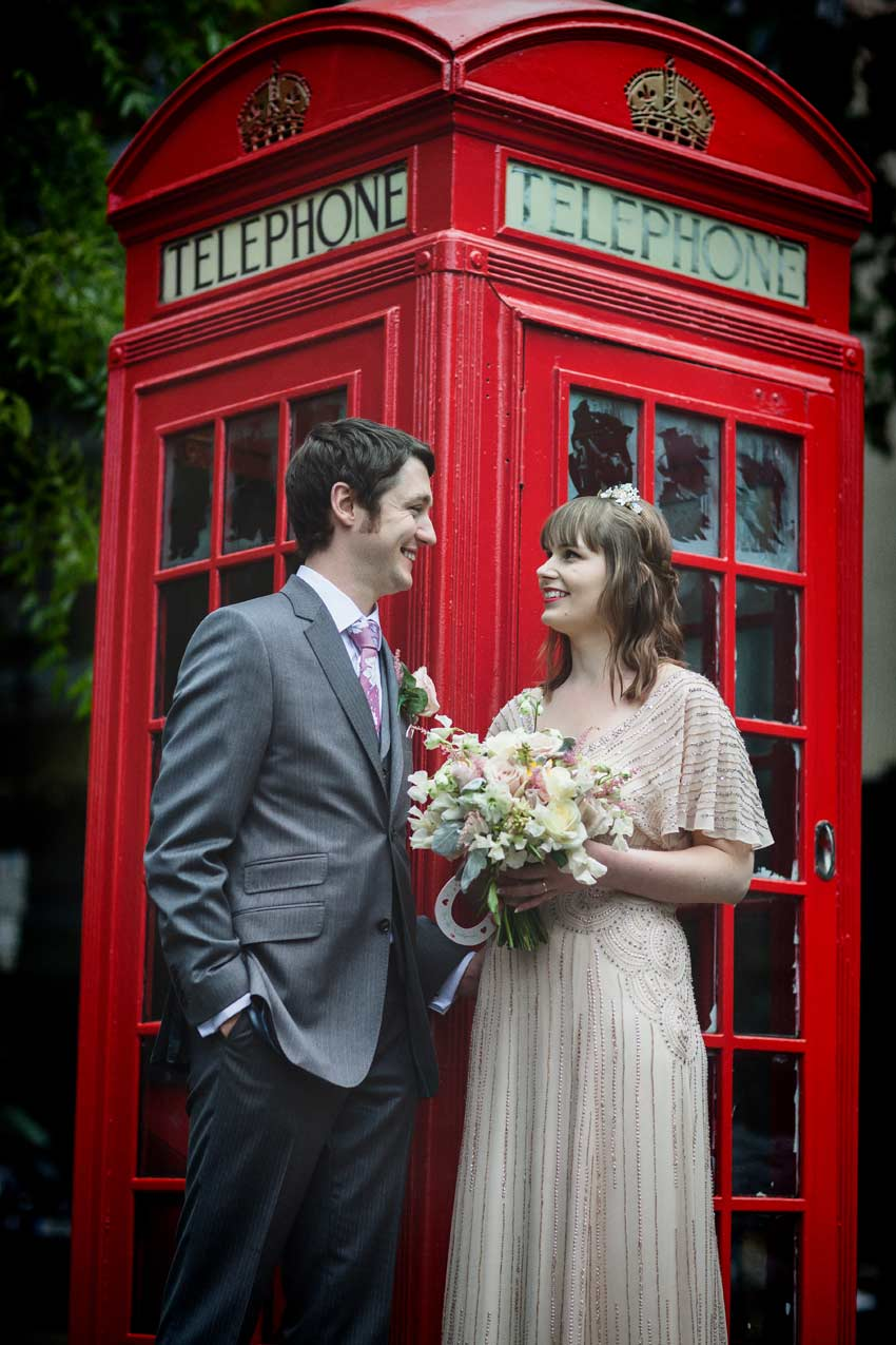 Islington bride and groom by red London phone box