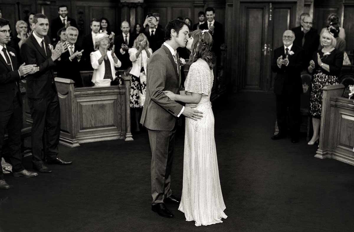 Wedding couple kiss in Islington town hall