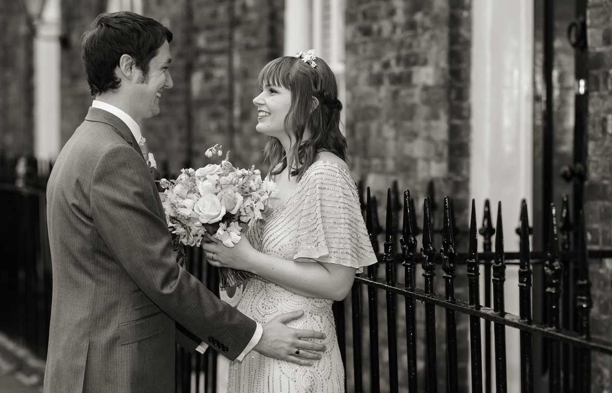 bride and groom laugh by Clerkenwell railings London