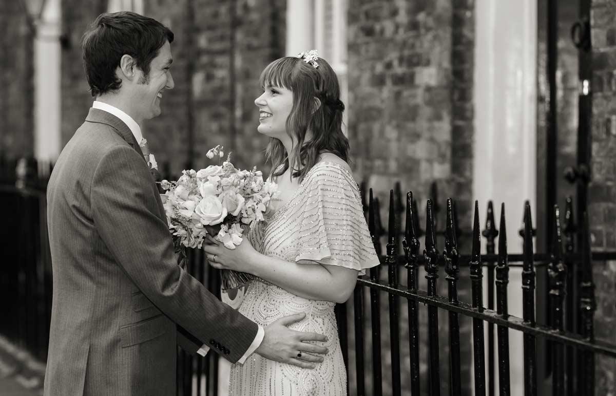 bride and groom laugh by Clerkenwell railings London