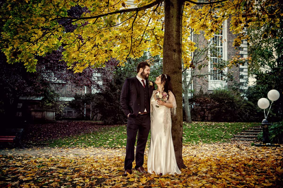 couple chat by tree and autumn leaves after their Islington wedding