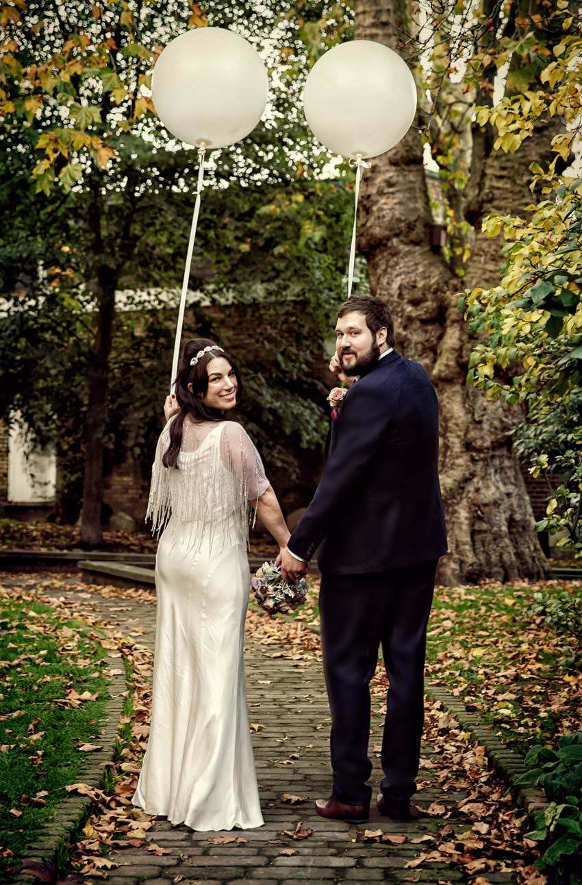 newlyweds turn round for photo on Islington footpath
