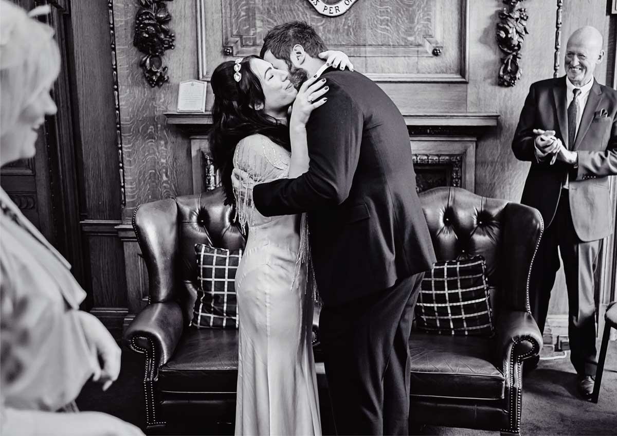 wedding couple hug and kiss at Islington town hall