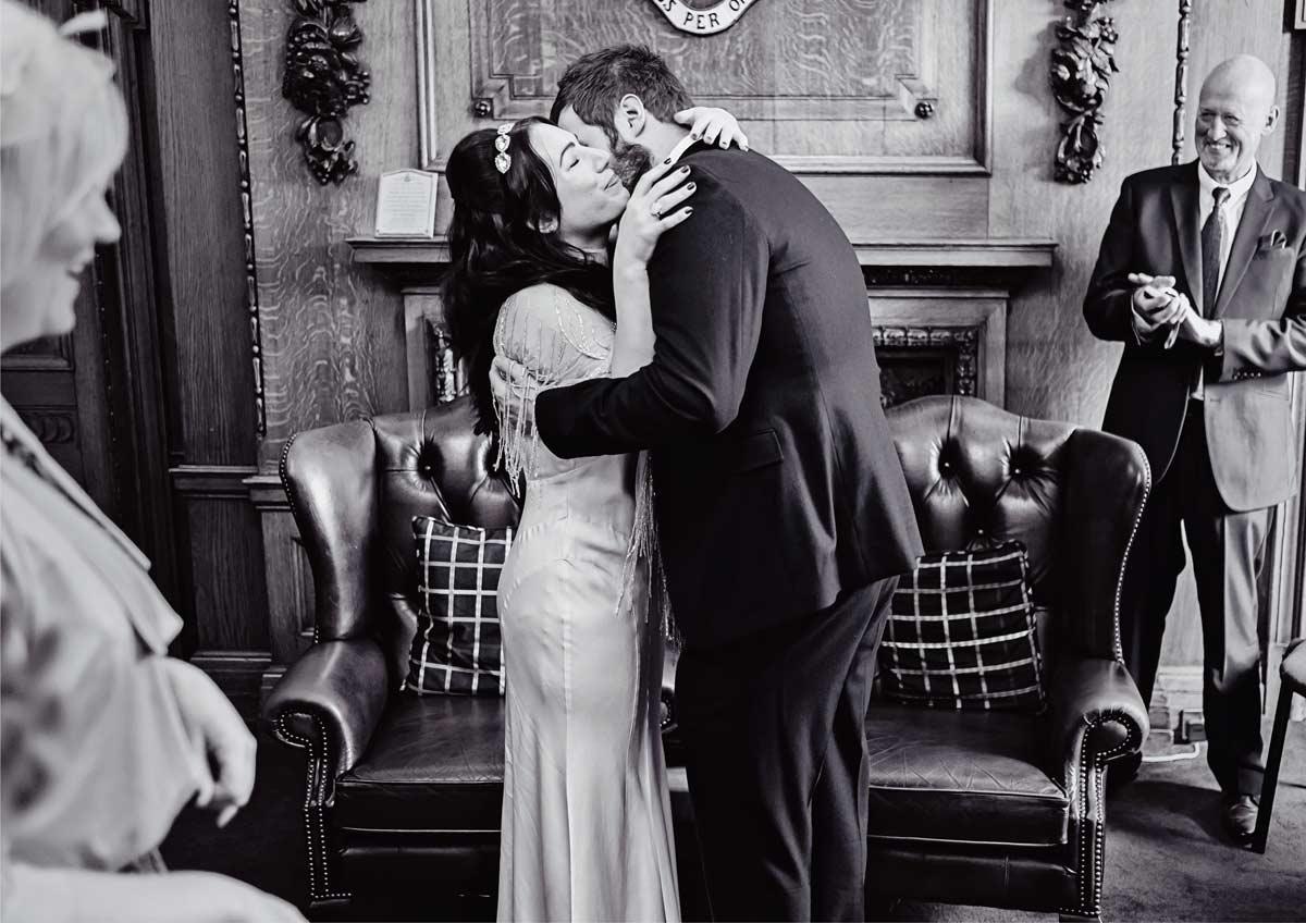 wedding couple hug and kiss at Islington town hall