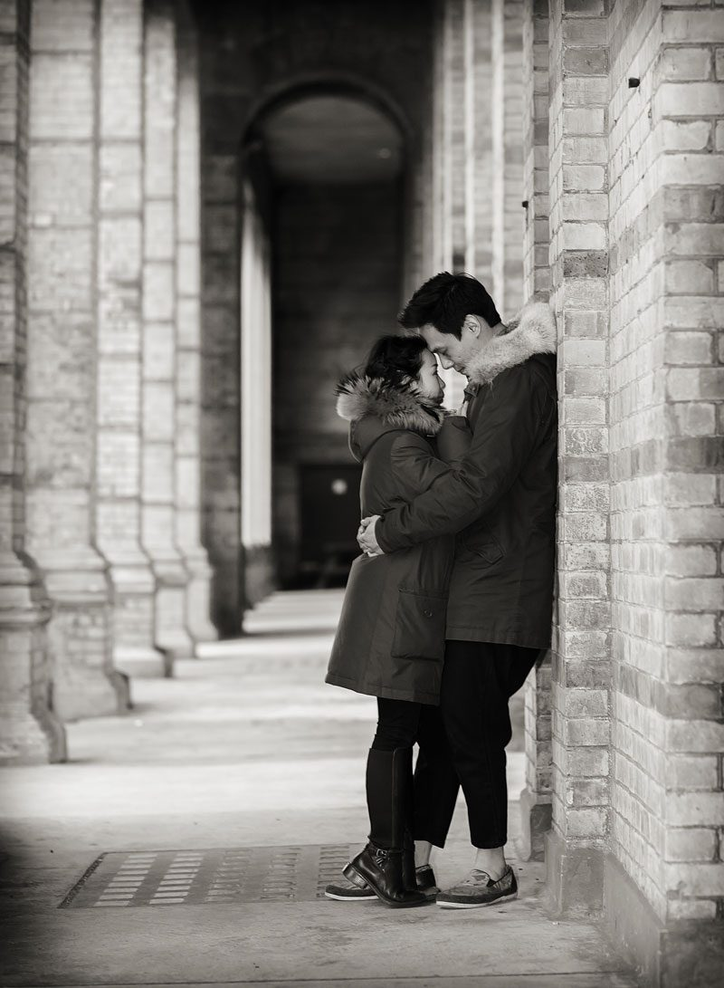 Couple cuddle under arches at Alexandra Palace