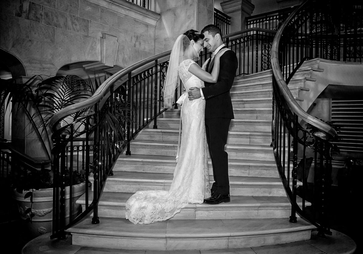 bride and groom hug on Landmark Hotel stairs