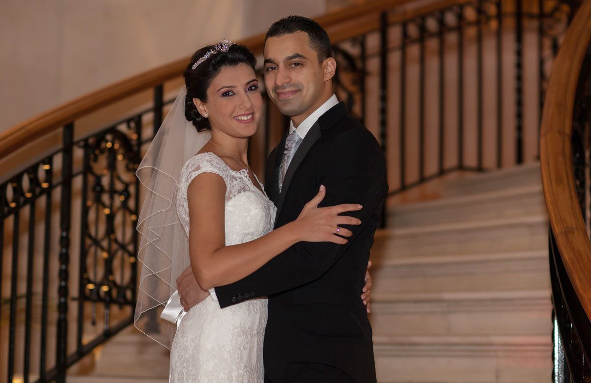 smiling wedding couple pose on white steps at Landmark Hotel
