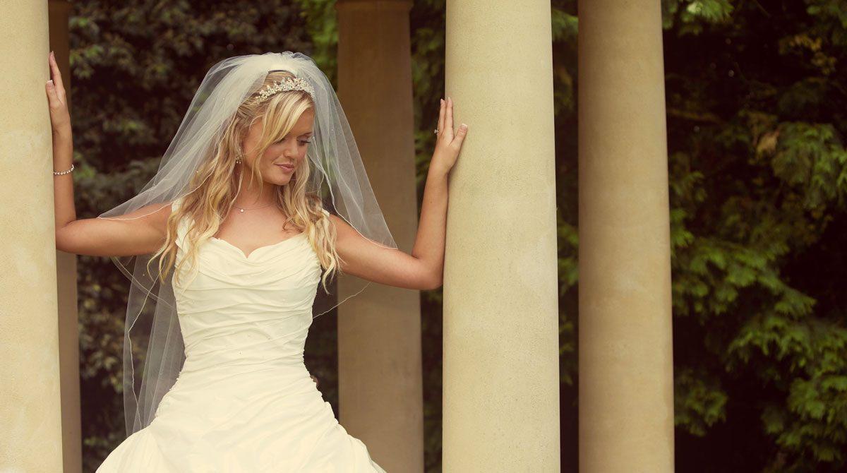 Bride between pillars West Lodge Park wedding day