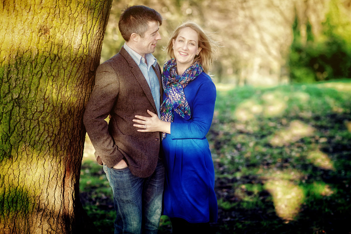 Engaged couple pose by tree at Alexandra Palace
