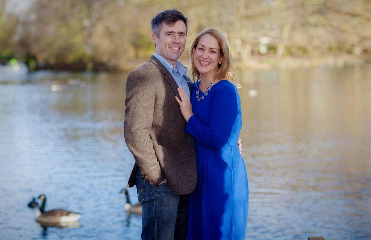 Engagement couple smiling at boating lake