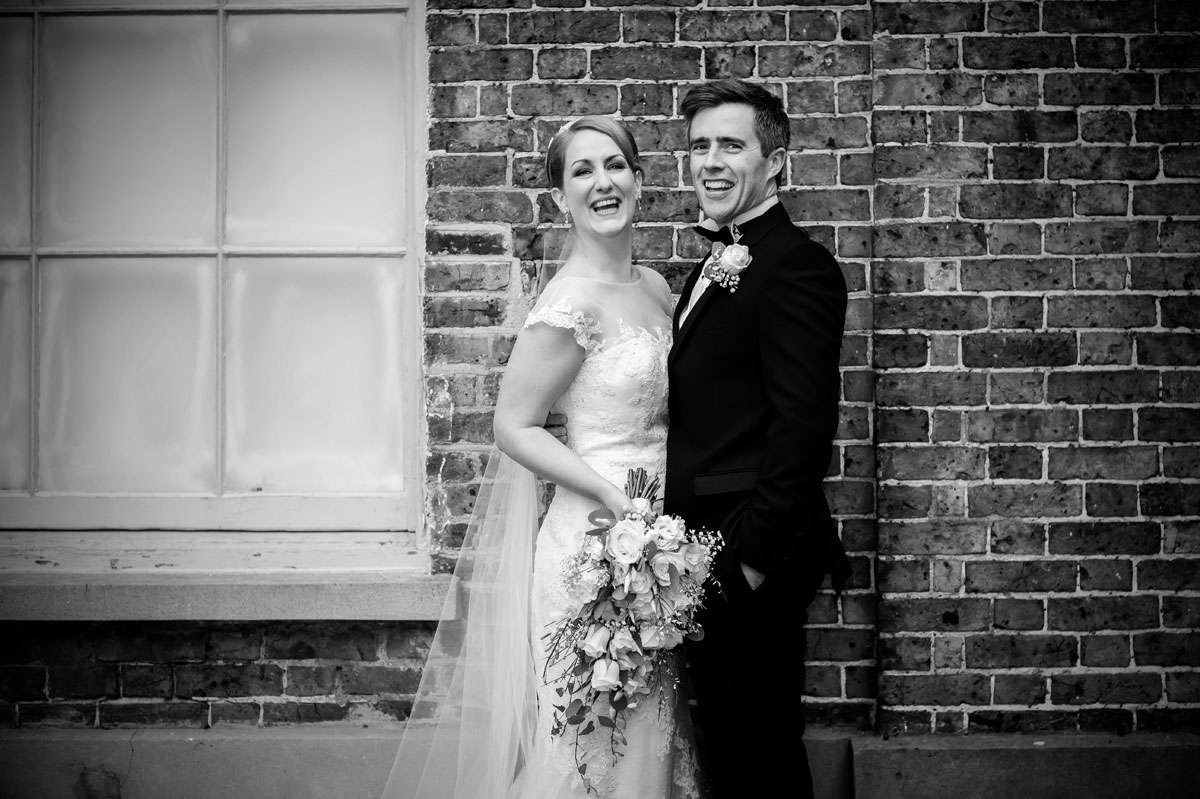Laughter at Hampton Court wedding black and white image