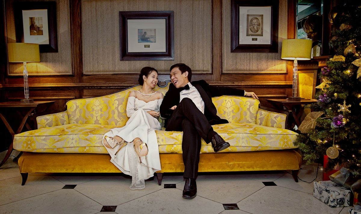 Laughter on the sofa downstairs at Goring Hotel wedding photo