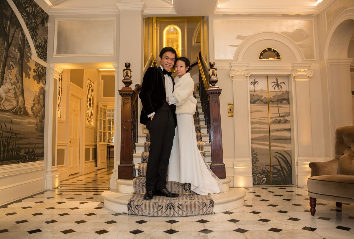 wedding couple pose on the stairs at The Goring Hotel