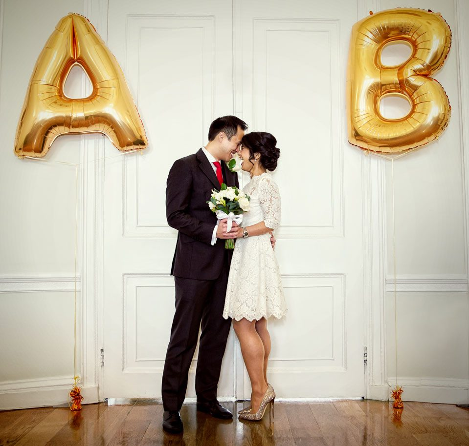 wedding couple laugh inside Asia House with balloons