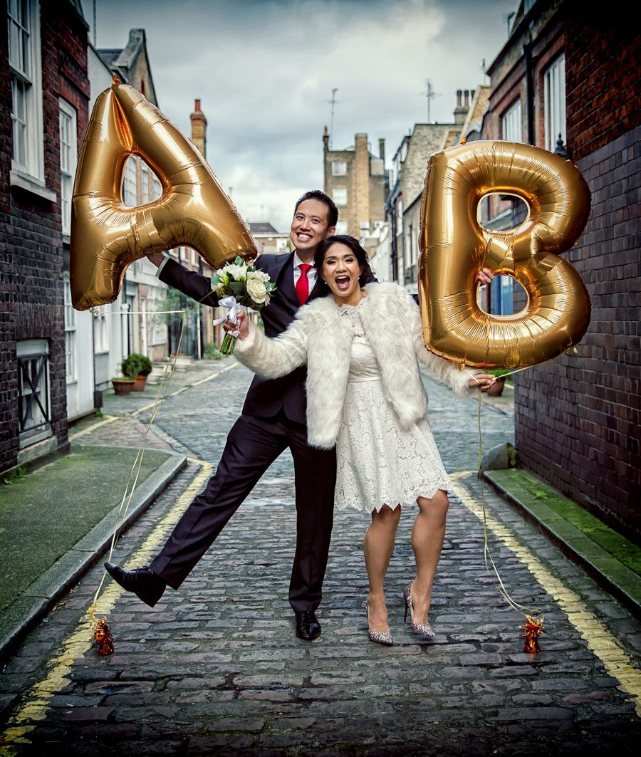 wedding couple pose with balloons on their central London wedding day