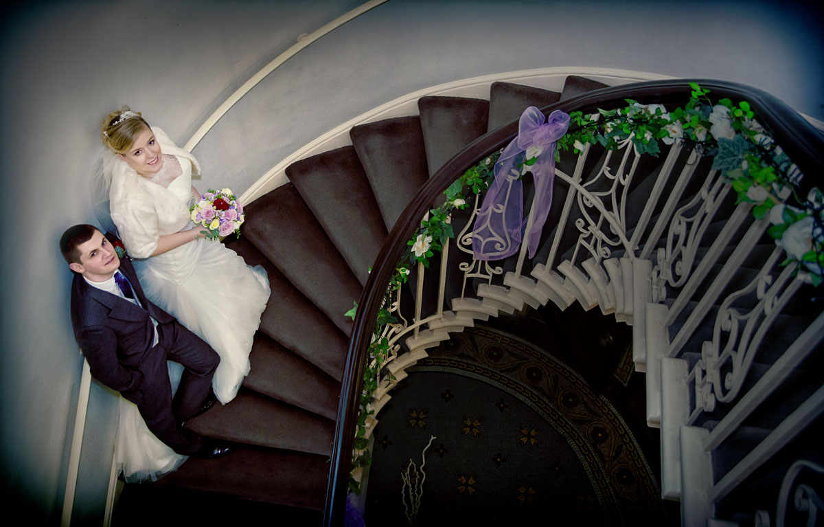 Wedding couple pose on stairs at Theobalds Park
