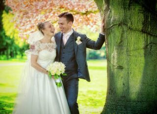 couple laugh by tree at Fanhams Hall wedding in Hertfordshire