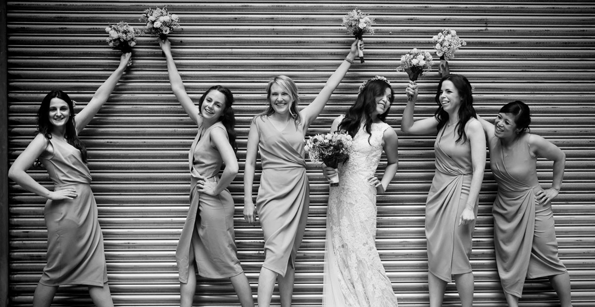 Bridesmaids pose in front of central London roller doors photo