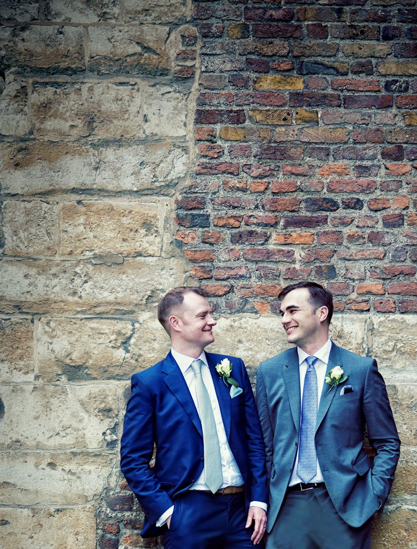 London male wedding couple pose by wall