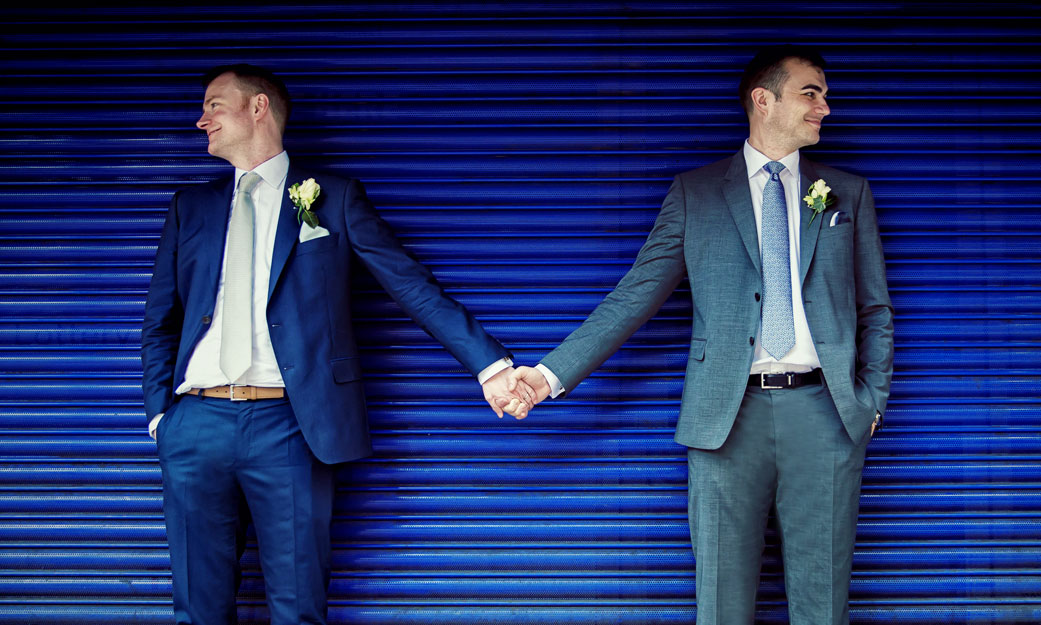men hold hands on their London wedding day