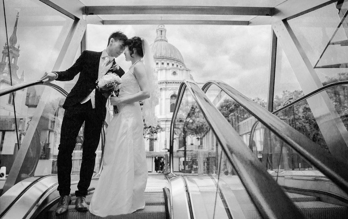 Bride and groom on escalator by London St Pauls Cathedral