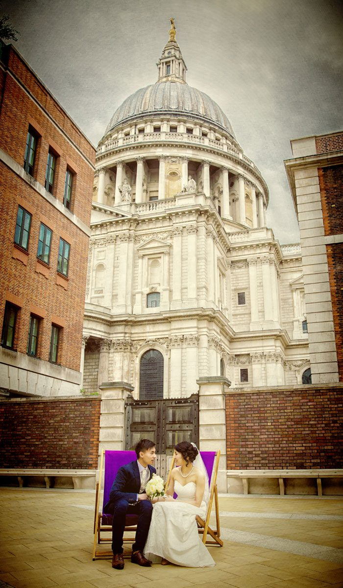 Wedding couple on deckchairs by St Pauls cathedral London