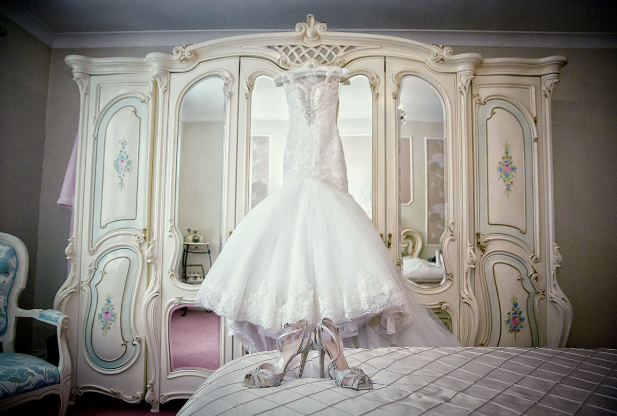 Italian wedding dress and shoes in brides bedroom photo