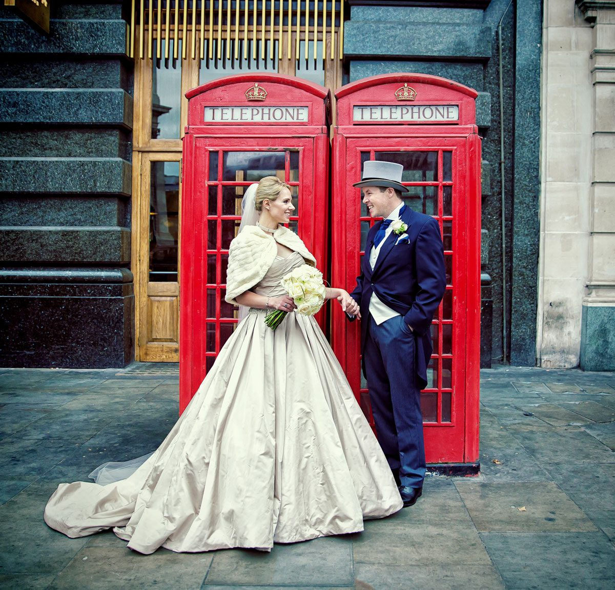 Bride and groom by red London phone boxes at their St Pauls wedding