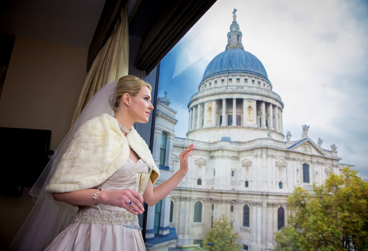 Bride looks from hotel window at St Pauls Cathedral on wedding day