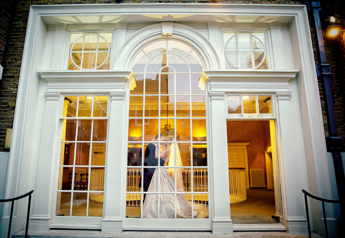 Couple kiss in front of window at Skinners Hall wedding reception