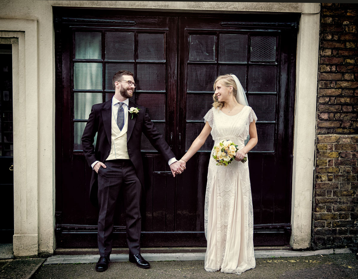 Couple pose by garage doors at Mayfair wedding