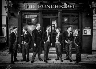 Groom and ushers laughing at Mayfair wedding photographer