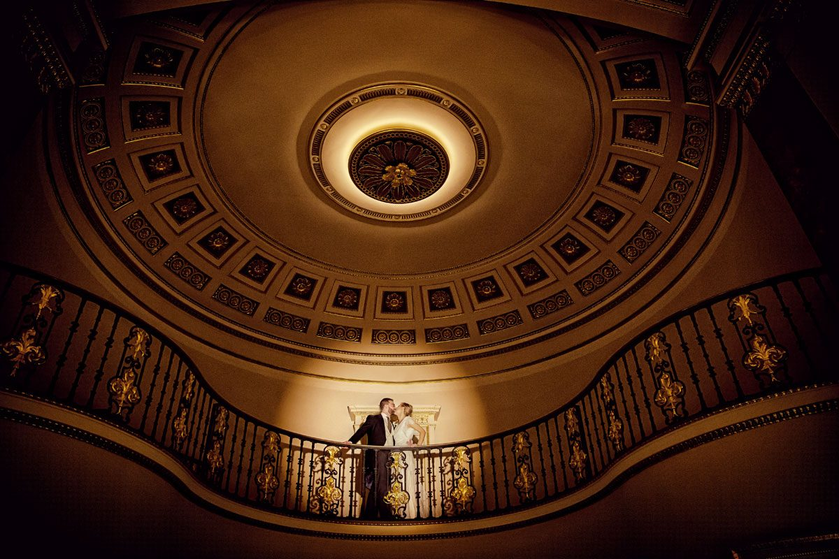 Lansdowne Club wedding photographers kiss in ballroom spotlight