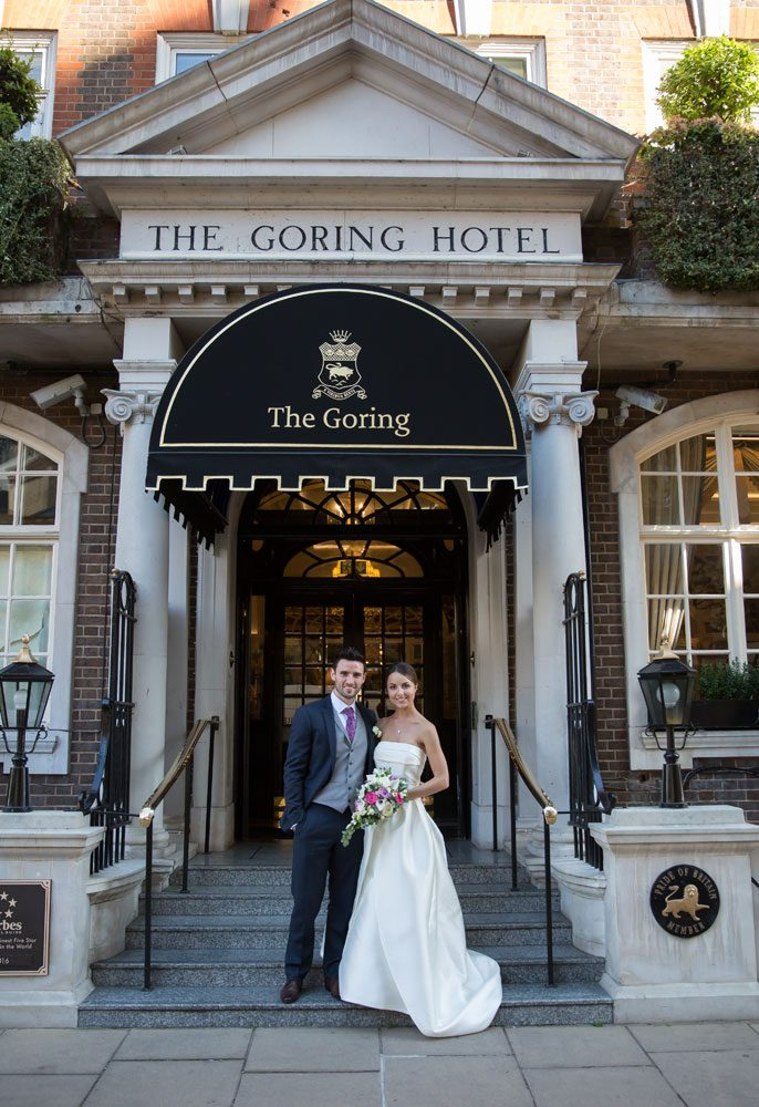 Wedding couple pose outside The Goring Hotel