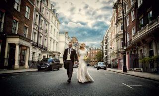 Wedding couple walk in middle of road in Mayfair London