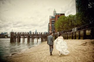wedding couple walk on beach at South Bank to Oxo Tower image