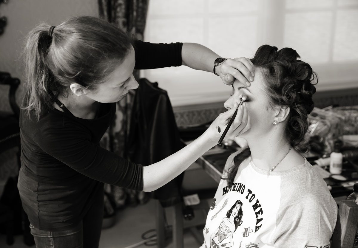 Bride has makeup applied at HAC wedding day image