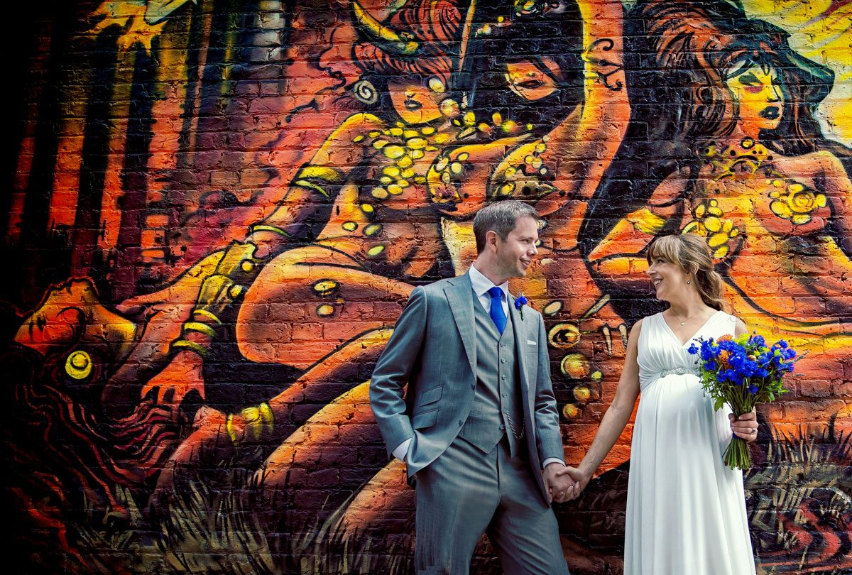 East London wedding couple in front of graffiti photo
