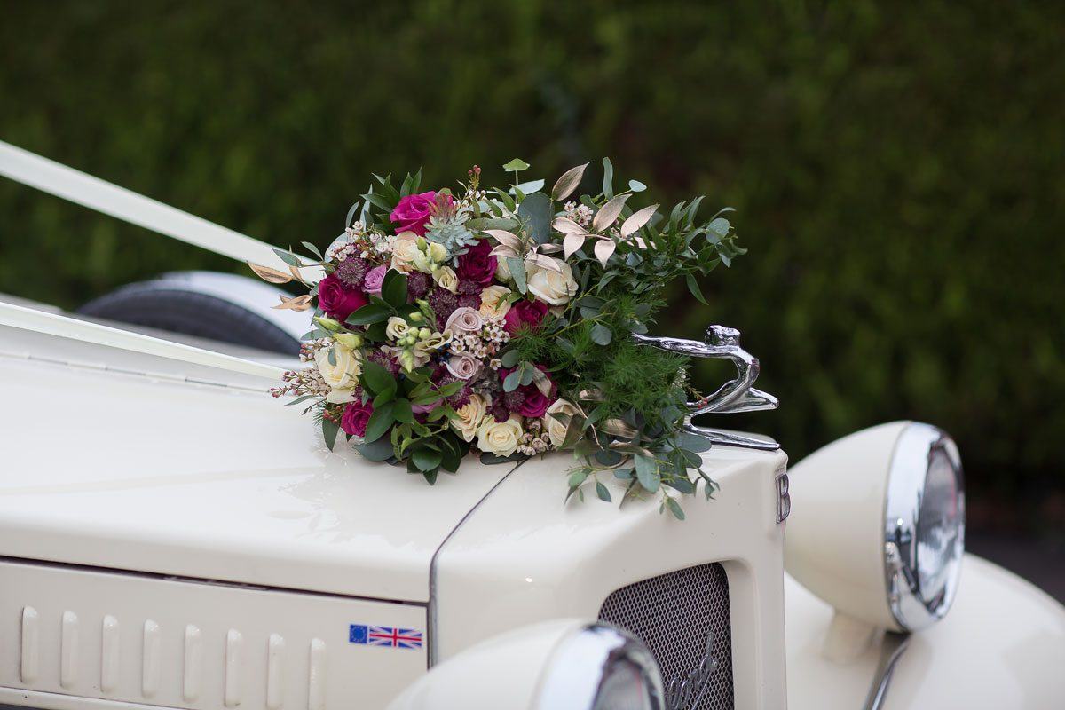 Wedding bouquet resting on vintage Bentley limousine image