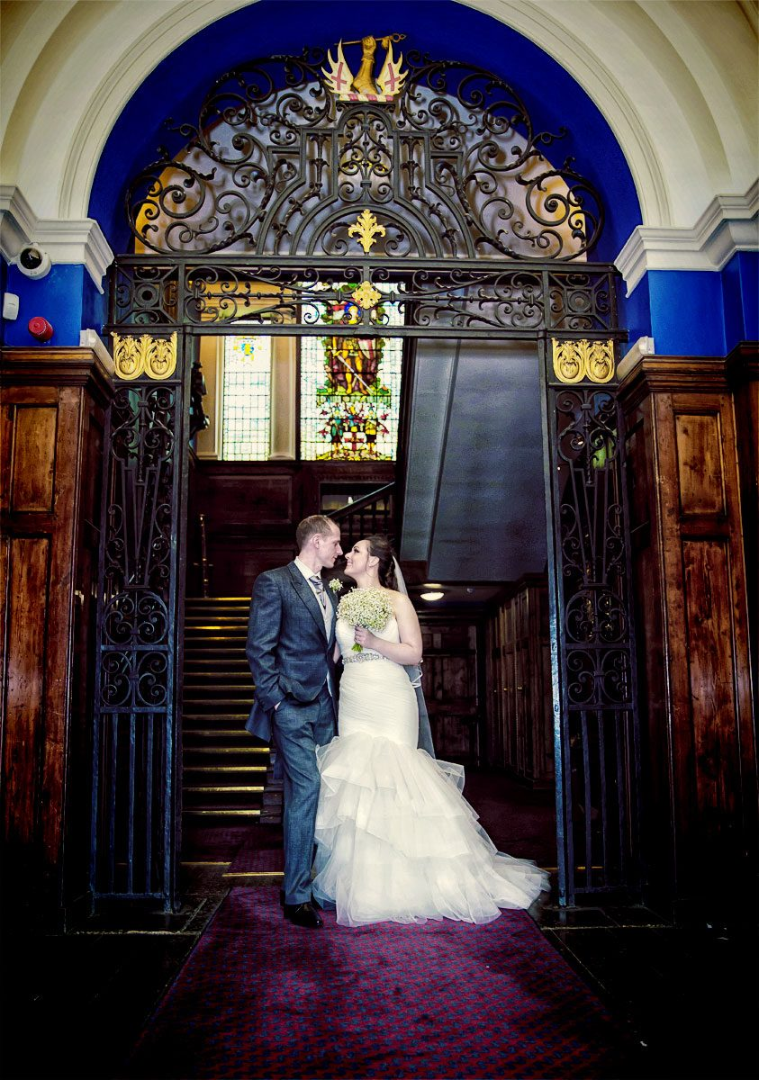 Wedding couple stand in arch at Armoury House wedding